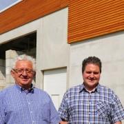 """Josef Tenk, Andre Tenk und Dipl.-Ing. Manfred Robers (v.l.) stehen vor der erst in diesem Jahr neu bezogenen """"Halle 11"""" des Unternehmens."""
